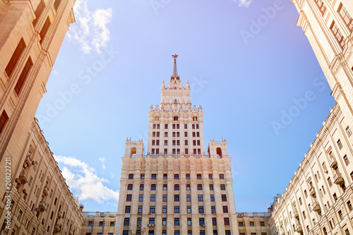 Fotobehang Moskou Russia style of Stalinist architecture against a blue sky with white clouds, view up. Welcome to the football world championship June 2018, Moscow, Russia
