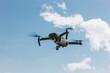 Leinwanddruck Bild - controlled modern drone flying in blue sky