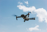 controlled modern drone flying in blue sky - 208228212