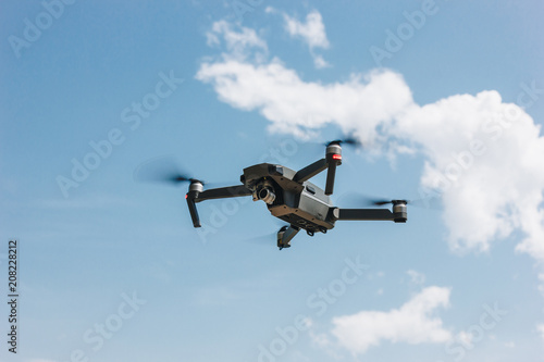 controlled modern drone flying in blue sky