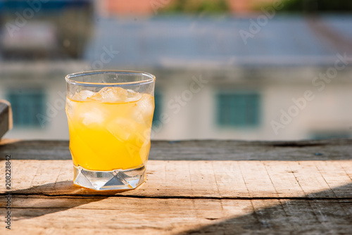 Fotobehang Sap Full glass of orange juice close-up. Fresh orange juice on wooden table in out of focus unidentified restaurant in the morning in summer