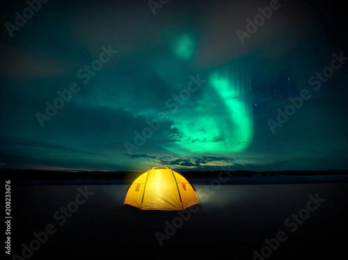 Fotobehang Noorderlicht Out in the wilderness The Norther lights ( Aurora Borealis) dances across the night sky in Sweden, above the glowing lights from the camping tent. Photo Composite.