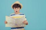 niño con sombrero y mapa sobre fondo azul - 208235281