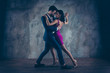 Leinwanddruck Bild - Full size body portrait of lovely attractive couple standing close in tango position face to face dancing, charming lady in purple tight dress gentlemen in tux isolated on grey background movement