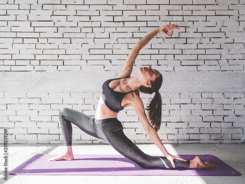 Plakat Portrait of attractive woman doing exercises. Brunette with fit body on yoga mat. Healthy lifestyle and sports concept. Series of exercise poses.
