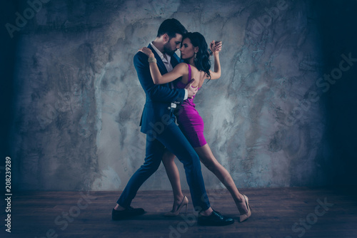 Leinwanddruck Bild Full size body portrait of lovely attractive couple standing close in tango position face to face dancing, charming lady in purple tight dress gentlemen in tux isolated on grey background movement