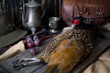 Hunted pheasant on a wooden board with metal and leather details like holandese naturmorn