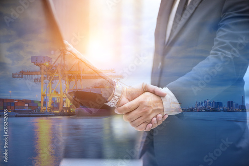 Fototapeta Logistic partner, Two businessmen shaking hand with Industrial port loading container, Cargo logistic import and export