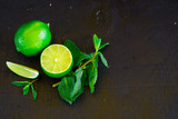 Fresh pices of lime and mint on black background. Free space