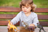 Toddler kid playing with a toy dinosaurs outdoors