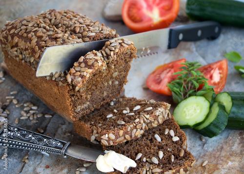 Fototapeta angeschnittener Brotlaib mit Butter, Gurke und Tomate zum belegen