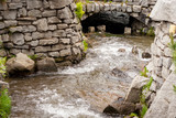 A mountain stream flowing between a stone wall - 208257034