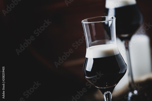 Two-layer cocktail with coffee liqueur, vintage wood background, selective focus - 208259405