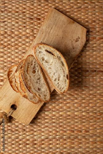 Rżnięta plasterka chleba seansu powietrza tekstura mąka na drewnianym bloku z wyplata tło i kopiuje przestrzeń.