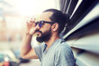 lifestyle, emotion, expression and people concept - happy smiling man with sunglasses and beard on city street - 208266816