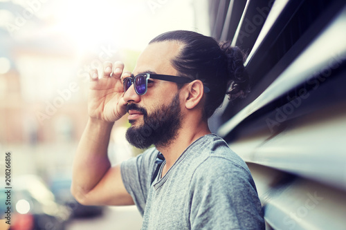 lifestyle, emotion, expression and people concept - happy smiling man with sunglasses and beard on city street