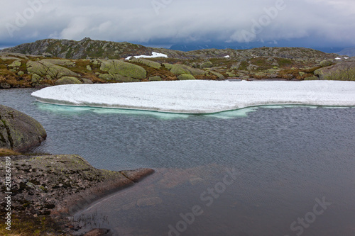 Fotobehang Bergrivier Frozen mountain lake on the Norwegian Scenic Route Ryfylke in overcast cool day in summer time, Norway. Snow in mountains does not thaw even in the summer