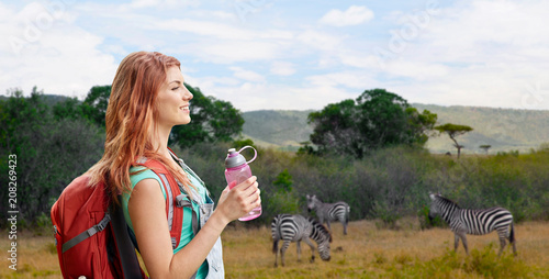adventure, travel, tourism, hike and people concept - smiling young woman with backpack and bottle of water over zebras in african savannah background