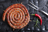 Grilled spiral sausages on a black background of charcoal.  - 208271448