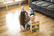 Cheerful mother playing with his baby girl on floor at living room