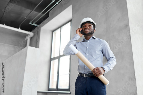architecture, construction business and people concept - african american architect in helmet with blueprint calling on smartphone