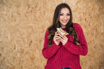 Shooting sideways a young cheerful girl with a beautiful smile in a modern cherry-colored sweater wants to eat her breakfast before work, holds a sandwich with bacon two hands. © romannoru