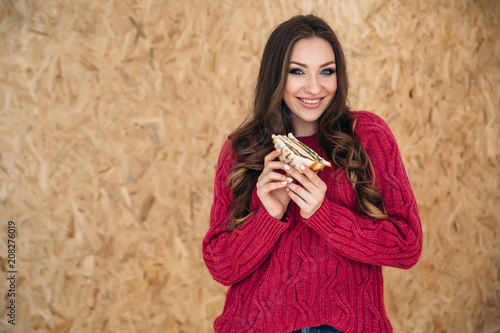 Fotobehang Kapsalon Shooting sideways a young cheerful girl with a beautiful smile in a modern cherry-colored sweater wants to eat her breakfast before work, holds a sandwich with bacon two hands.