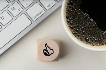 Würfel mit Daumen-Hoch-Symbol am Arbeitsplatz  © fotogestoeber