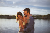Young couple in love flirting by the river at sunset - 208288498