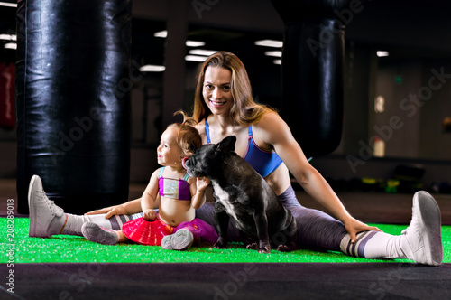 Poster Charming sports mom trains in the gym with her little daughter and a French bulldog.