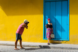 Man taking a photo of a girl against a yellow wall