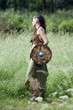 beautiful Celtic shieldmaiden in the field with shield