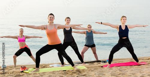 Wall mural Joyful sporty women practicing yoga positions