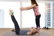 Partner workout. Two female friends doing abs exercises at gym
