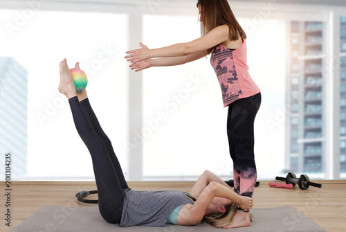 Sticker Partner workout. Two female friends doing abs exercises at gym