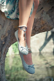 woman legs sit on tree in park  with anklets wearing light flat summer shoes - 208305845