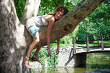 funny smiling young woman relaxing on tree in park summer day - 208306044
