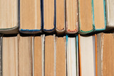 background, defocusing. Old books neatly stacked on the shelf