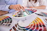 Close-up Of Two Architect Holding Colorful Swatch Over Blueprint - 208324235
