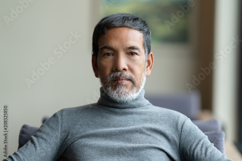 Portrait of attractive mature asian man retired with white stylish short beard sitting on couch at coffee shop cafe. Close up of old handsome businessman or entrepreneur in urban lifestyle concept.