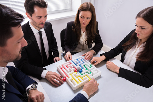Businesspeople Holding Multi Colored Arrow Solving Maze