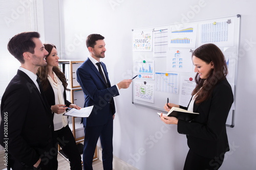 Businesspeople Analyzing Graphs On White Board