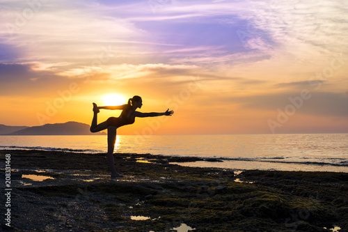 Fotobehang School de yoga young girl practicing yoga on the beach during the sunset.