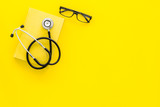 Medical literature. Stethoscope near book and glasses on yellow background top view copy space - 208334031