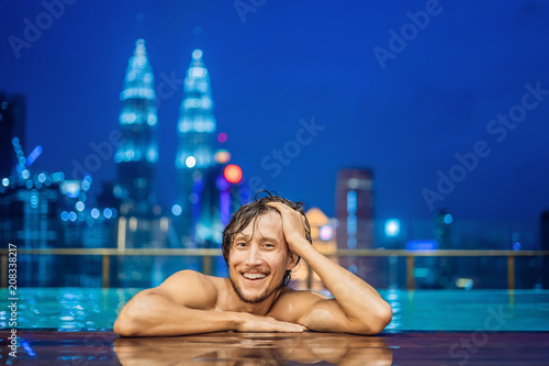 Fotobehang Donkerblauw Man in outdoor swimming pool with city view in blue sky