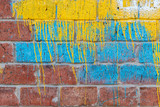 Multi-colored paint stains on the old brick wall