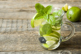 Fresh citrus lemonade in a glass of lime on a wooden background. Copy space for text