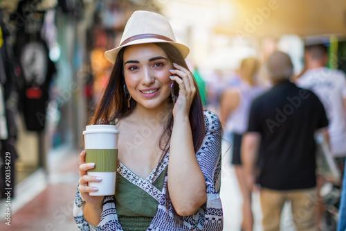 Attraktives, dynamisches Hipster Frau in der Stadt unterwegs mit Kaffee und Telefon in der Hand; City Lifestyle Konzept
