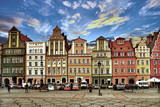 Central market square in Wroclaw Poland with old colourful houses, street lamp and walking tourists people at gorgeous stunning evening sunset sunshine. Travel vacation concept