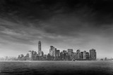 Dramatic panoramic view of storm over Lower Manhattan from Ellis Island at dusk, New York City. Black and white image.